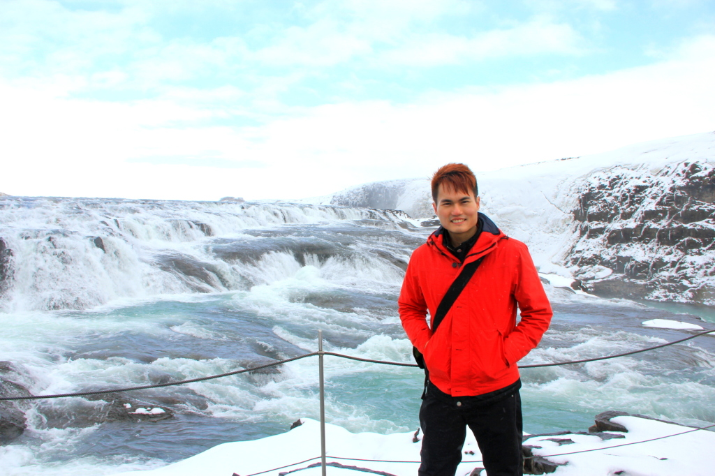 Embracing the icy cold waterfall in Iceland