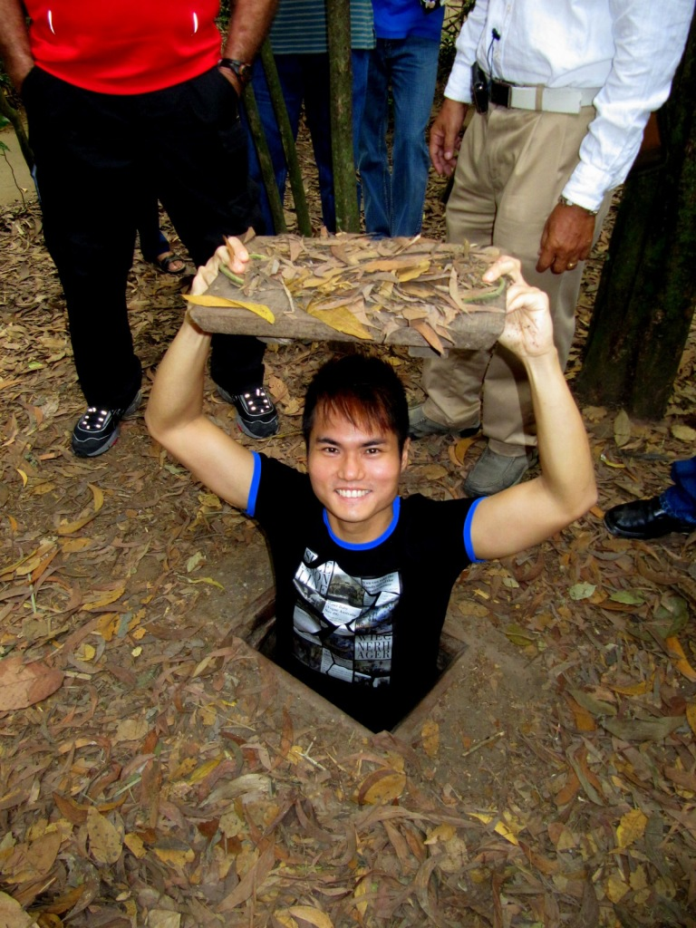 Taking a famous photo at Cu Chi Tunnel, Vietnam