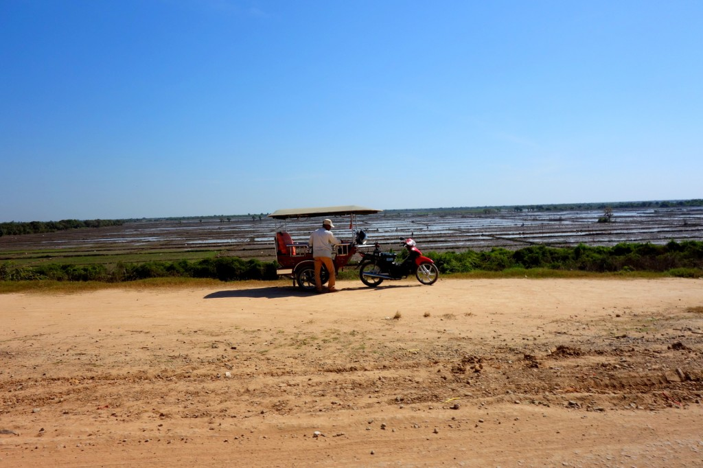 Cambodian chauffeur cleaning his tuk tuk in front of the rice field
