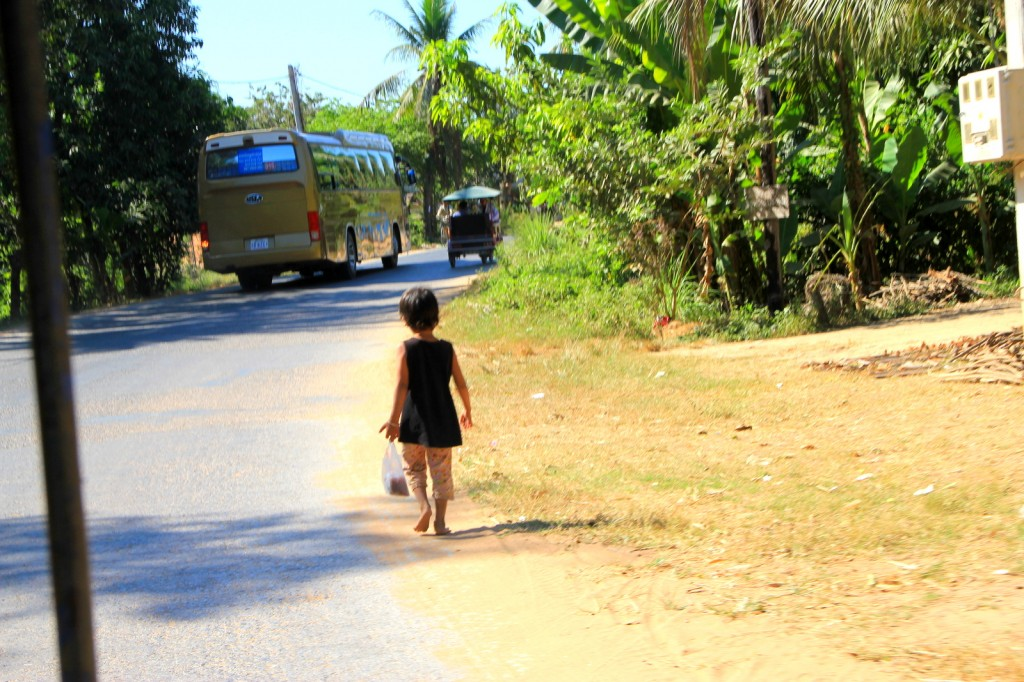 Little girl walking home barefoot with her grocery