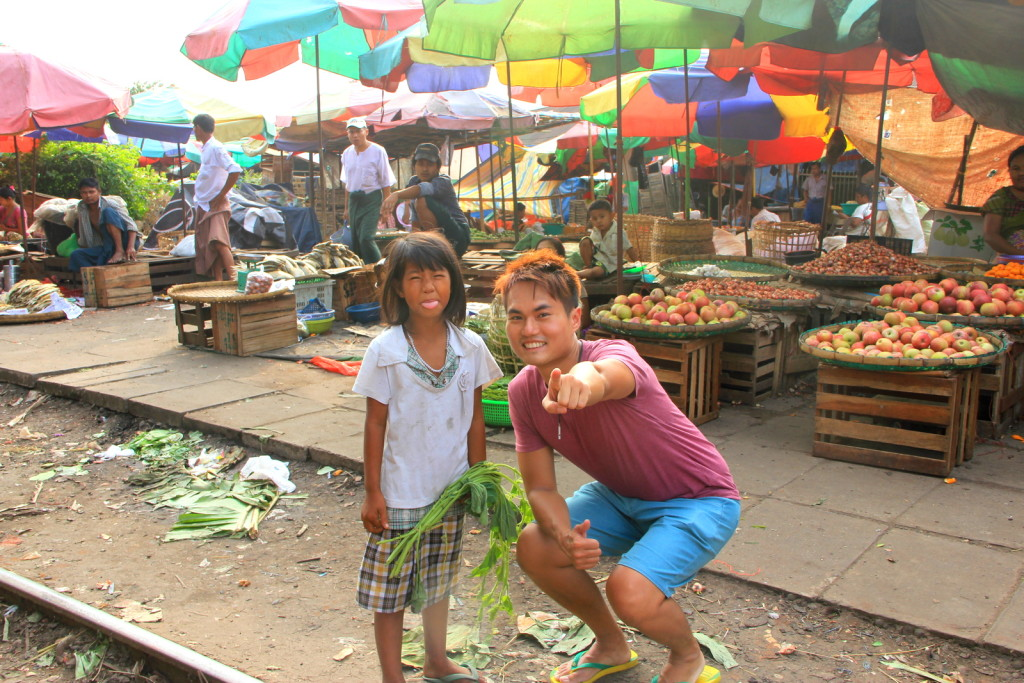 Little cute Burmese girl interacting with foreign tourist